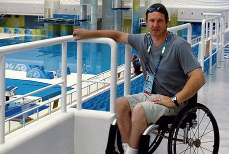 Image of Martin Mansell at the side of the pool in a wheelchair
